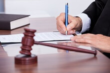 Person signing paperwork with a gavel nearby